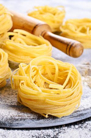 Tagliatelle yellow in dry form in the form of a slot on a floured surface