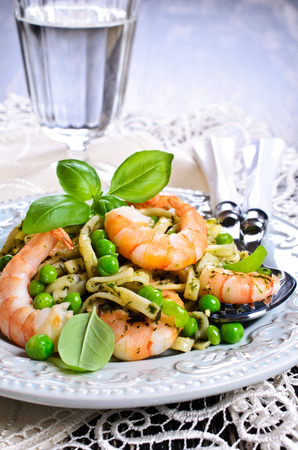 Pasta tagliatelle with shrimp and peas, dressed with sauce pesto