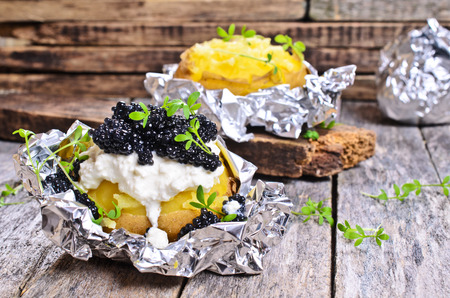 Potatoes baked in foil completely with cream cheese and black caviar Archivio Fotografico