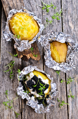 jacket potato: Potatoes baked in foil completely with cream cheese and black caviar Stock Photo