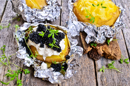 completely: Potatoes baked in foil completely with cream cheese and black caviar Stock Photo