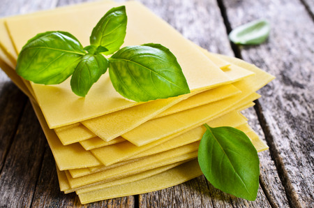 Sheets for lasagna with Basil leaves laid on a wooden surface Archivio Fotografico