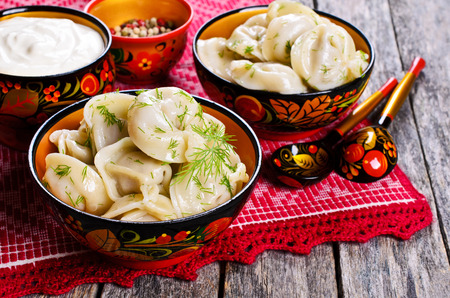 Dumplings with dill in a wooden plate in rustic style 스톡 콘텐츠