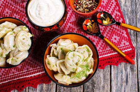 Dumplings met dille in een houten plaat in rustieke stijl