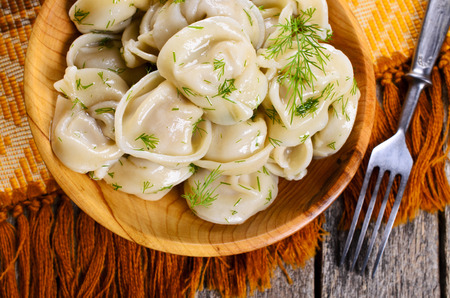 Dumplings with dill in a wooden plate in rustic style Imagens