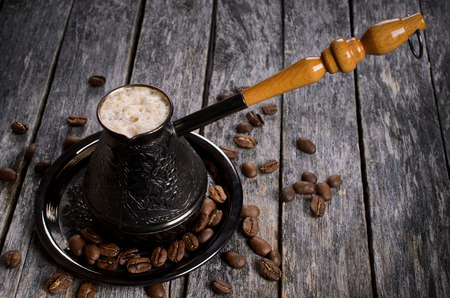 cezve: Welded a frothy coffee in cezve on a wooden surface in rustic style