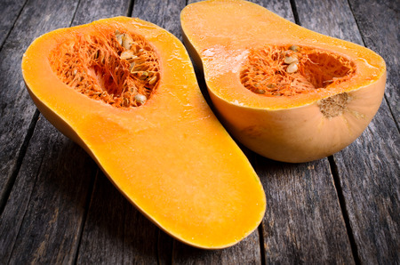 Butternut squash cut in half on a wooden surface