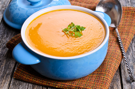 Pumpkin soup in ceramic bowl on wooden surface