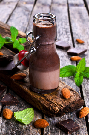cold background: Chocolate milk in a glass on a wooden surface