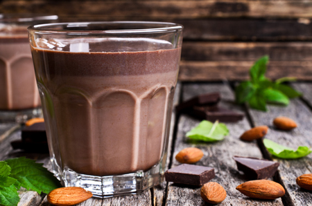 Chocolate milk in a glass on a wooden surface