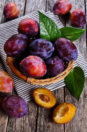 Fresh plum with water drops on wooden surface Archivio Fotografico