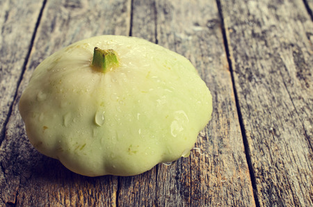 Fresh ripe white squashes on a wooden surface
