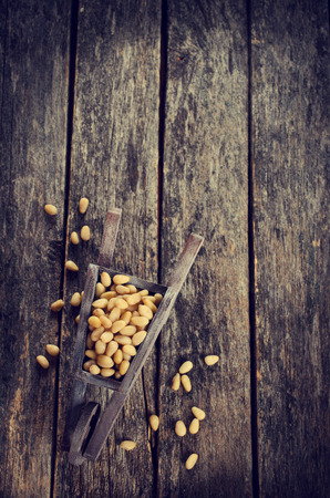 pine kernels: Pine nuts peeled on wood furniture in rustic style Stock Photo