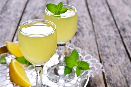 Drink of lemon in a small glass on a wooden surface 스톡 콘텐츠
