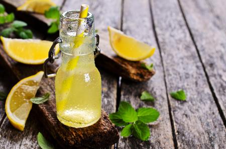 木製の表面の小さなガラスのレモンの飲み物