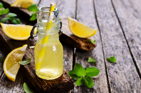 Drink of lemon in a small glass on a wooden surface Imagens