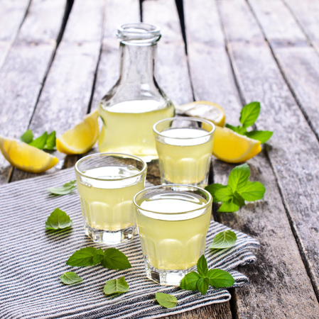 Drink of lemon in a small glass on a wooden surface Standard-Bild