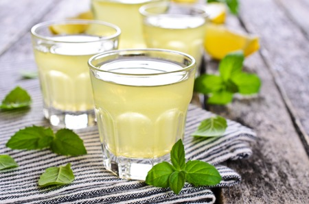 Drink of lemon in a small glass on a wooden surface Archivio Fotografico