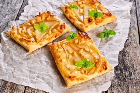 tartlet: Tart with pears and nuts on the baking paper.