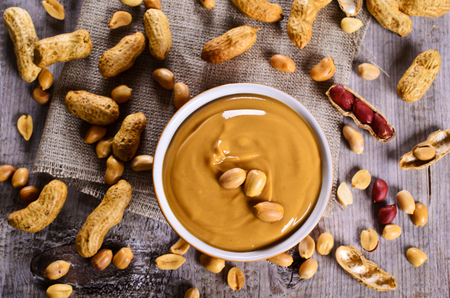 Peanut butter in a ceramic dish on the background of whole nuts. Selective focus.
