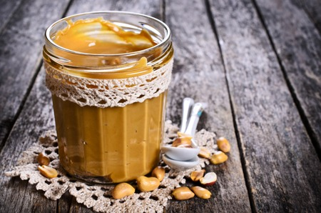 Peanut butter in a glass container on a wooden surface. Selective focus.