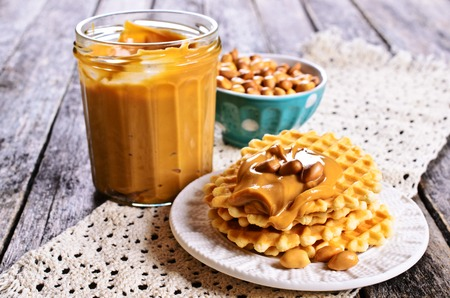 Waffles with peanut butter in a ceramic bowl on a wooden surface. Selective focus.