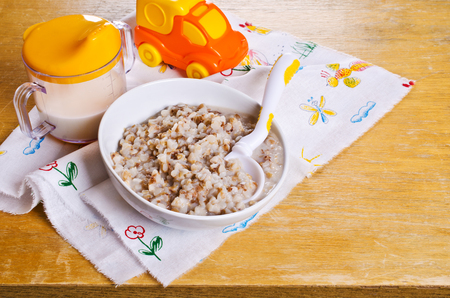 Porridge buckwheat with milk for baby food in a ceramic plate