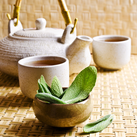Leaves of fresh sage on a background of ceramic cups with tea Archivio Fotografico