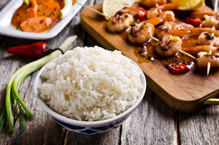 White rice cooked on a background of shrimp on skewers and salad with carrots. Selective focus. Archivio Fotografico