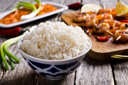 エビ串とニンジンのサラダの背景に白いご飯。選択と集中。