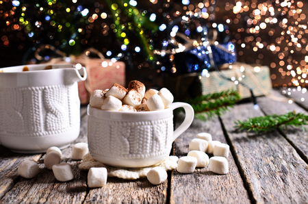 Hot drink with marshmallows on the background of Christmas decorations