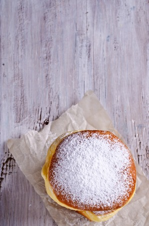 donut style: Donut in powdered sugar on a wooden background in rustic style. Selective focus.