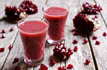 turbid: Pomegranate liqueur with cream in a glass on a wooden surface. Selective focus. Stock Photo