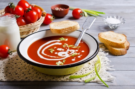 tomato puree: Tomato puree soup with cream in a metal bowl on a wooden background. Selective focus. Stock Photo