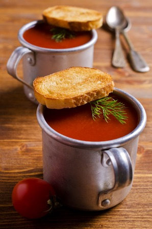 tomato puree: Tomato puree soup  in a metal bowl on a wooden background. Selective focus.
