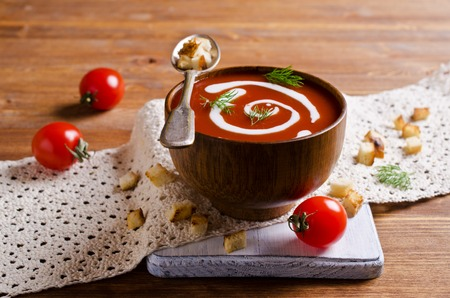 tomato puree: Tomato puree soup with cream in a wood bowl on a wooden background. Selective focus.