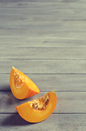 Pumpkin slices with seeds on a wooden background. Selective focus.