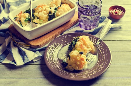 Casserole with cauliflower and spinach on a wooden background. Selective focus. Archivio Fotografico