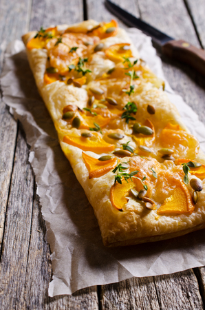 Tart with pumpkin and cheese on wooden background. Selective focus.