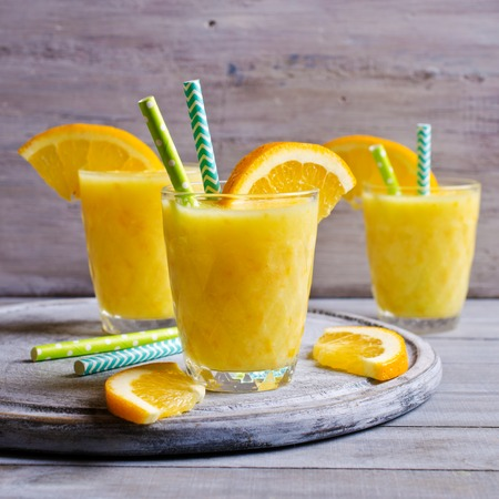 Thick drink made from citrus fruits in glass bowl on wooden background. Selective focus.