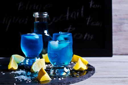 full shot: Blue drink with ice in a glass on a wooden background. Selective focus. Stock Photo