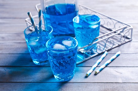 blue hawaiian drink: Blue drink with ice in a glass on a wooden background. Selective focus. Stock Photo