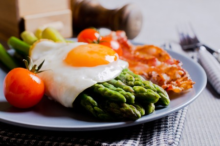 eggs and bacon: Green asparagus with fried eggs, bacon and tomatoes. Selective focus. Stock Photo