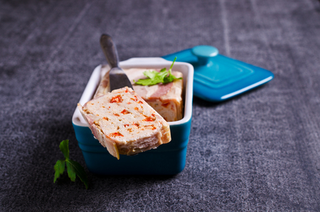 Meat terrine with bacon and paprika on a dark background. Selective focus.