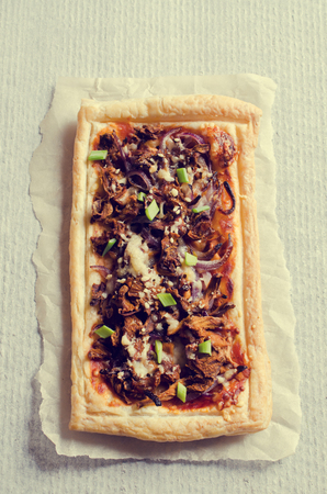 puff pastry: Tart of puff pastry with mushrooms and onions. Selective focus. Stock Photo