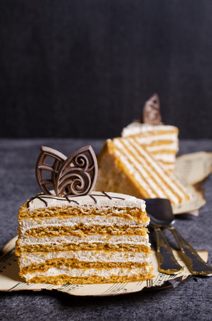 Slices of homemade cake from layers of cream and a dark background. Selective focus.