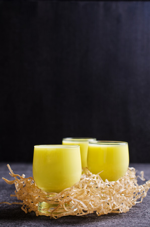 aperitive: Yellow liquid in a glass on a dark background. Selective focus. Stock Photo