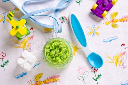 Baby food of peas on the table against the background of toys. Selective focus. Imagens