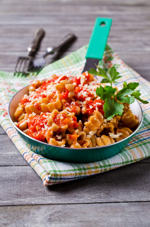 Pasta with vegetable sauce on wooden background. Selective focus.
