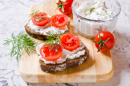 Sandwich with cream cheese, tomatoes and dill. Selective focus.